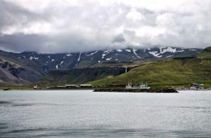 ocean in Iceland in front of mountains with snow and cloudy sky - The Country Jumper