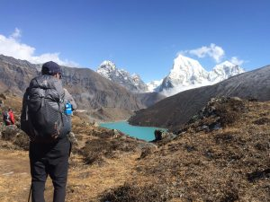 man wearing Gregory optic backpack in front of mountains and lake