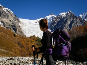 woman with purple backpack standing in front of snow covered mountains with Gregory Jade