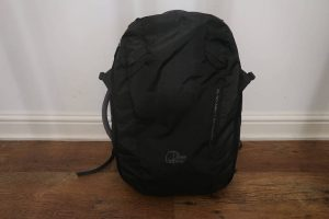 black backpack leaning against white wall