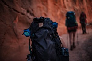 people wearing backpacks traveling through a red rock canyon