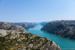 blue water running through fjord in Norway - two cliffs on either side, photo taken from above - The Country Jumper