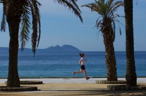 woman running between palm tress in front of Cies Island