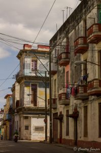 tall apartment building along the side of a street with electrical wires in Havana, Cuba - The Country Jumper