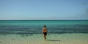 Woman in pink and black biking walking in blue water in Eleuthera Island, The Bahamas