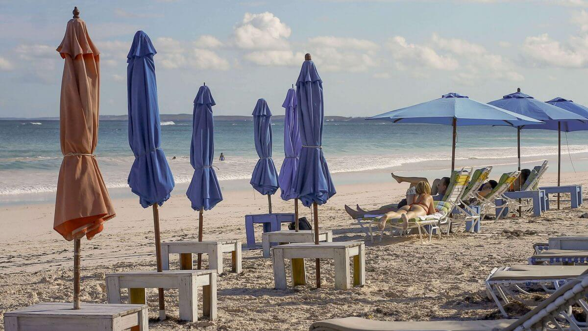 blue and pink umbrellas, white sun loungers, girl sun bathing on pink sands beach harbour island the bahamas