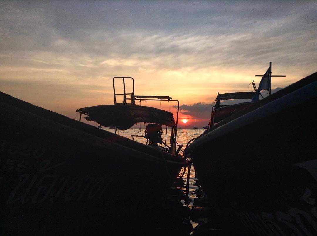 The sun setting behind two boats in the harbor at Railay Beach Thailand