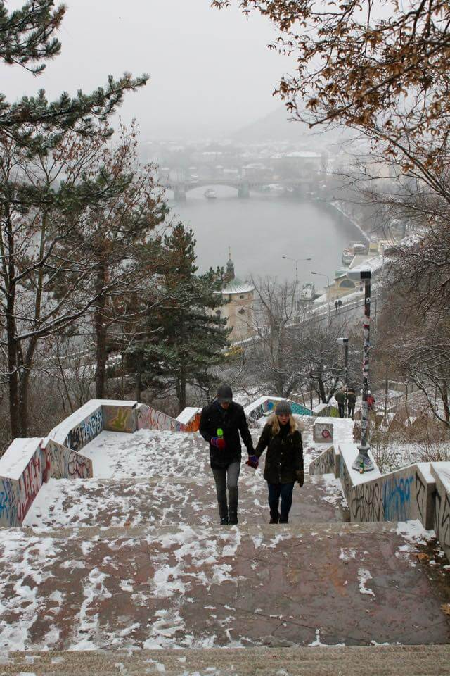 A couple walking up the snowy steps of Letna Park in Prague