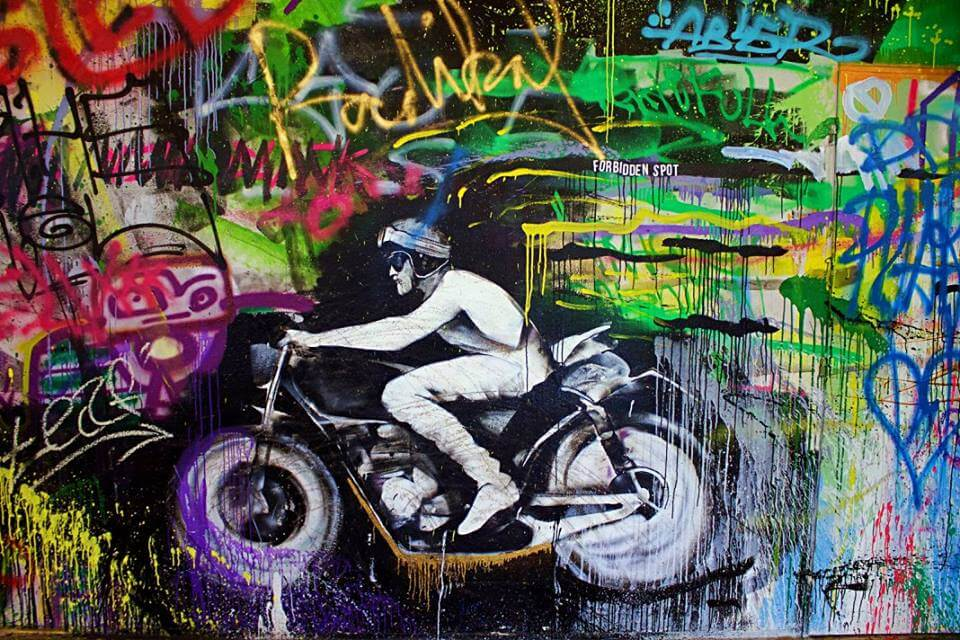 motorcycle graffiti on colorful wall at the forbidden spot in Prague. non touristy things to do in Prague