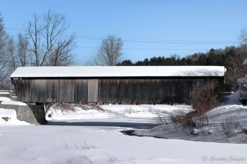 snow covered covered bridge across icy river below blue sky