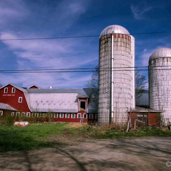 red barn with two grain silos beneath blue cloudy sky