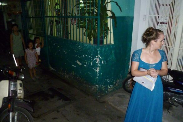 white girl standing in Vietnamese alleyway in ballgown