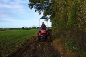 woman driving red tractor through countryside in France