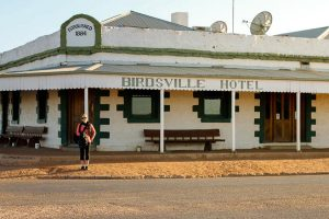 woman standing in front of Birdsville hotel in Australia - The Country Jumper