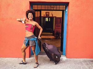 woman wheeling backpack in front of orange wall