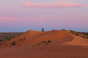 jeep sitting a top of a sand dune - Big Red - in the Australian Outback - The Country Jumper