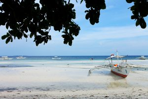 boat on white sand beach in The Philippines