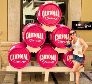 woman with blue fan standing in front of pink Cartojal barrels at Malaga Feria