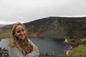 blonde woman in gray sweater standing next to lake in Ireland - world's largest Guinness - the country jumper