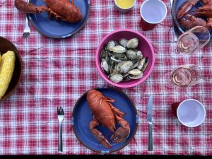 lobsters and steamers and corn on the cob on a red and white checkered table cloth