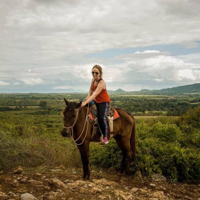 girl in red shirt sitting on brown horse in cuban mountains - horse back riding in Cuba