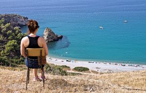 woman in black top and Joanne shorts sitting in chair looking at the blue ocean along the costa del sol Spain - the country jumper