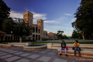 two women sitting on a fence on UCLA campus in sumer