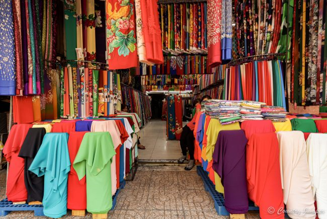 colorful fabrics hanging from ceiling and on mannequins in fabric market stall in Vietnam