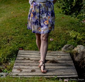 woman's legs wearing sknne length purple skirt with flowers, walking over wooden bridge in garden