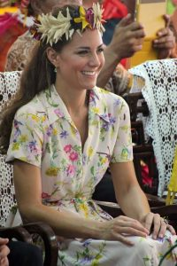 Kate Middleton wearing floral crown and floral dressing sitting and smiling
