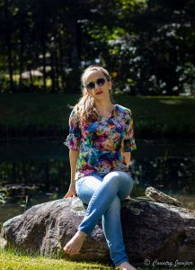 blonde woman sitting on rock in front of pond wearing sunglasses, lipstick, multi colored shirt, and jeans