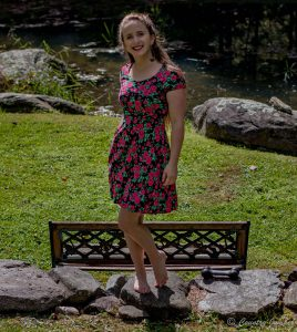 woman standing on stone wall behind bench wearing pink floral dress