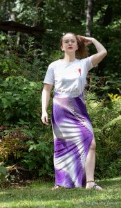 woman standing on grass wearing white shirt and purple maxi skirt with one leg sticking out through high slit