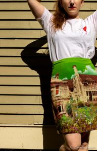 woman standing against side of house with white t-shirt and green skirt with picture of house