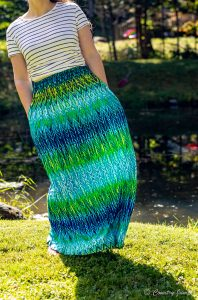 long maxi skirt worn by woman - cannot see face - skirt is blues and greens - hands in pocket - standing on grass
