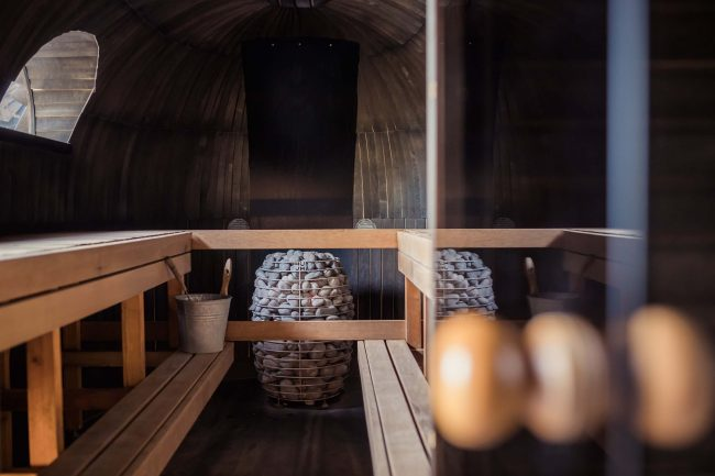 benches around edge of small, wooden sauna room