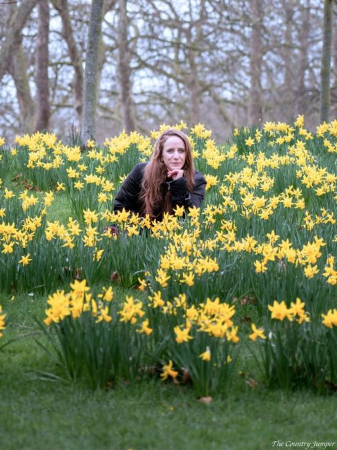 woman with long hair and wearing a black jacket sitting amongst yellow daffodils