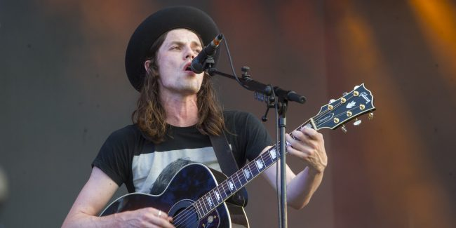 Man with long hair and black hat singing into microphone and playing guitar