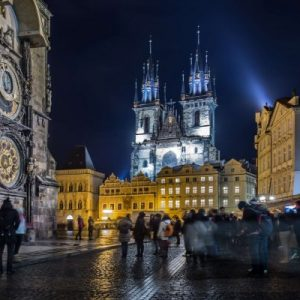 Prague's astronomical clock on left, old town square in front with lights at nighttime