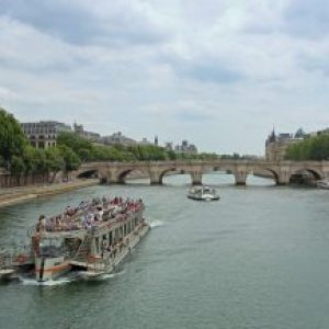tour boat on river seine with bridge in background